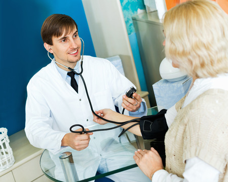 Young smiling male pharmaceutist taking  mature patients blood pressure using  sphygmomanometer in pharmacy drugstore