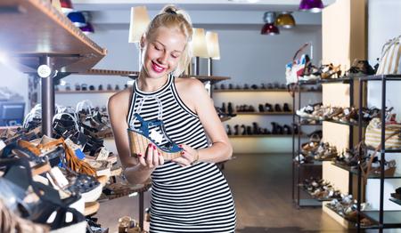 joyful smiling blonde girl in dress choosing pair of shoes in boutique