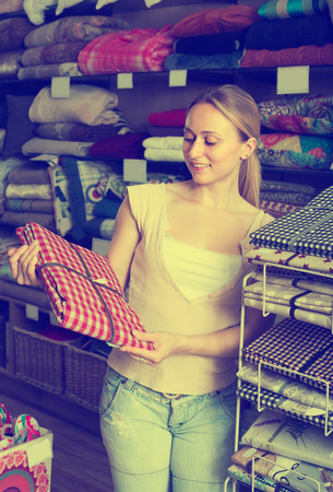 happy woman customer picking cotton tablecloths in textile department