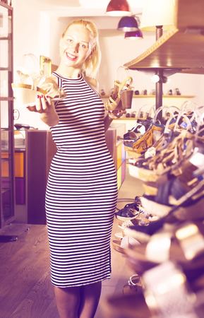 Young cheerful girl choosing from two pairs of shoes in boutique
