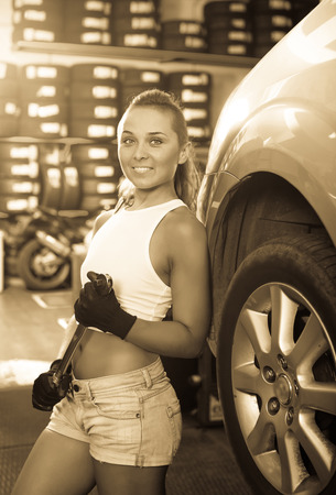Happy young mechanic woman working on car wheel in service point