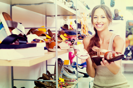glad young woman searching for pair of new shoes in fashion shop