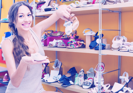 Portrait of cheerful smiling positive young woman looking after pair of shoes for kid in fashion store