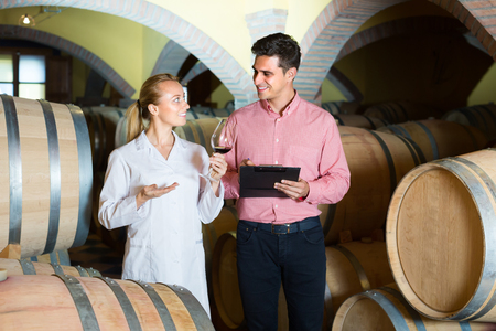 cheerful  male client and wine factory staff discussing wine from wooden barrels