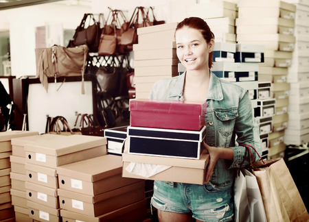 Cheerful teenager girl holding boxes with chosen pairs in shoes boutique