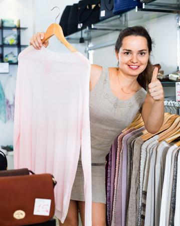 Smiling woman choosing new long sleeve blouse in apparel shop