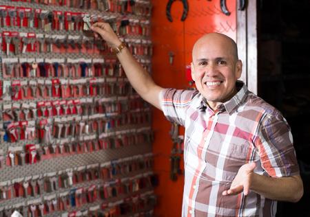 handyman posing with duplicates of door keys in workshop