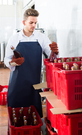 adult spanish male employee packing wine bottles at sparkling wine factory