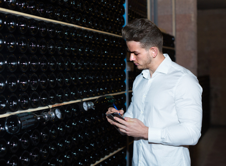 Young man 20s worker controlling secondary fermentation of wine at sparkling wine factory