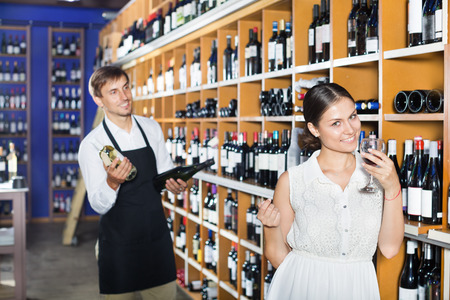 Young cheerful woman holding a glass of wine before buy it in wine house
