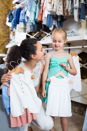 smiling mother with daughter buying baby pajamas in white color in kids section