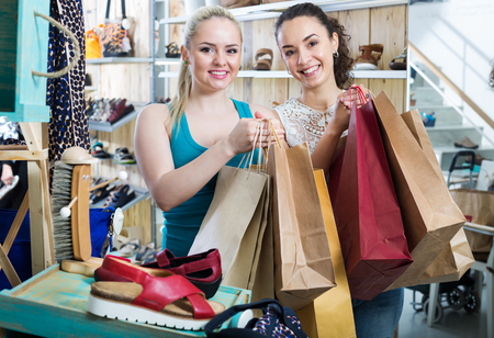 Two happy glad young women shopping shoes and looking happy with a purchases. Focus on both persons