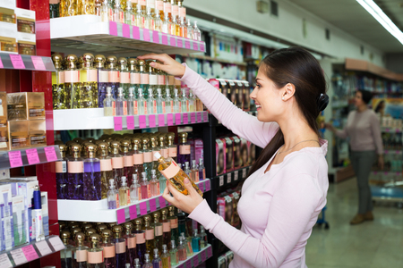 Happy brunette young girl and mature woman choosing perfume in beauty department