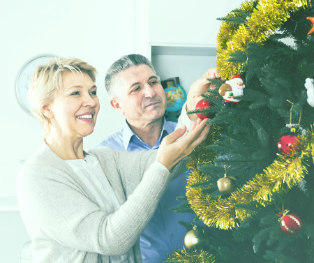 Mature couple decorate fir-tree for holidays of Christmas and New Year at home
