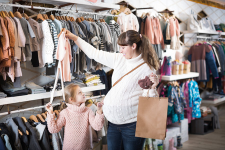 Positive pregnant woman and child choosing clothes for baby in store