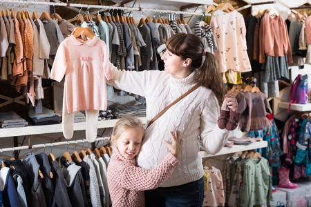 Positive pregnant female and small daughter choosing clothes for baby in children?s cloths shop