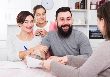 Photo pour Young parents signing papers for new house with their daughter - image libre de droit