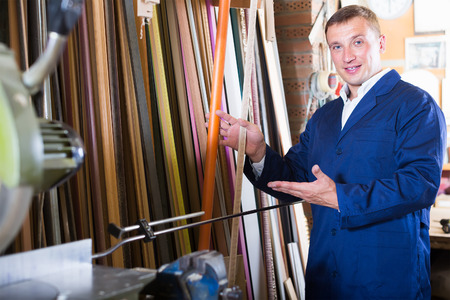 Photo pour cheerful male seller standing in picture framing studio with wooden details - image libre de droit