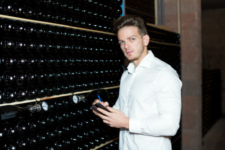 Glad male worker checking secondary fermentation of wine at sparkling wine factory