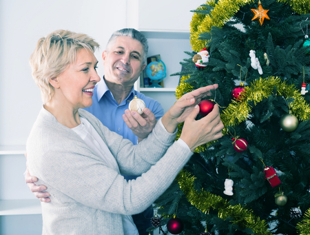 Mature positive couple decorate fir-tree for holidays of Christmas and New Year at home