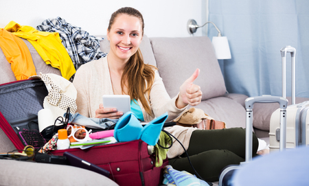 Young glad woman packing luggage for holidays at home