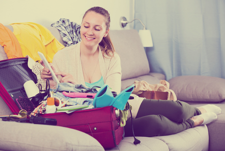 Young happy woman getting ready for vacations at home
