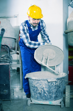 Glad young worker starting to work with cement mixer at workshop