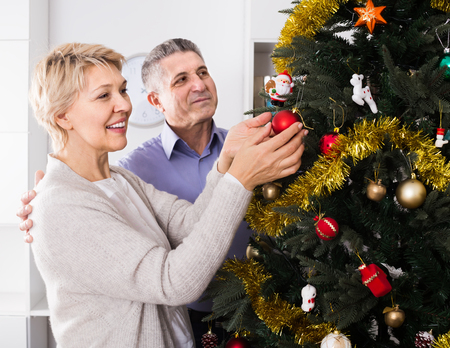 Mature happy couple decorate fir-tree for holidays of Christmas and New Year at home