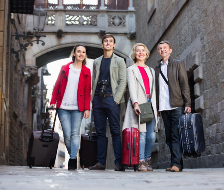 Happy smiling satisfied family of four with trunks and bags on European city street