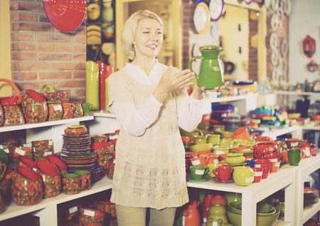 Senior blonde woman chooses ceramic ware in the cookware section at hypermarket