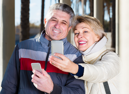 husband and wife make selfie on cell phones for walk on sunny day outdoors