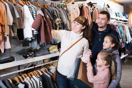 Smiling family with children examining clothes for new baby in children's cloths shop. Focus on man