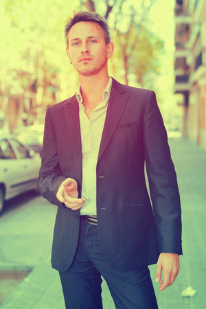Portrait of respectable young man strolling through city streets