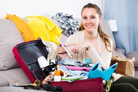Young cheerful woman getting ready for vacations indoors