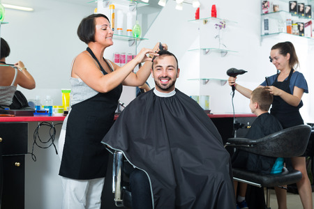 joyful woman hairdresser making hairstyle of smiling man in beauty salonの写真素材