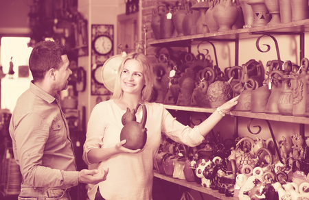 portrait of happy european  man and woman shopping ceramic utensil in boutique