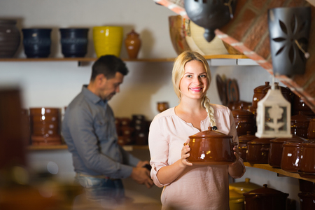 Cheerful female customer picking crockery in ceramics workshop