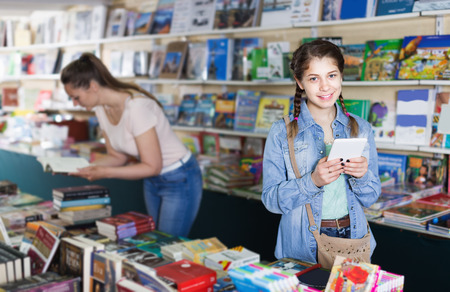 Positive schoolgirl with screen tablet at books store