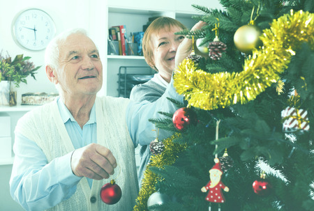 Husband and wife hang up New Year's toys on fir-tree before Christmas holiday