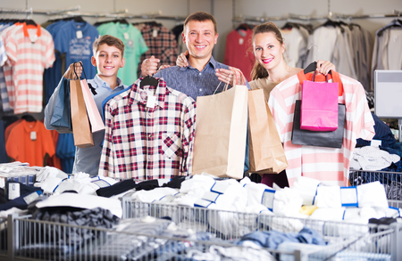 Happy family shows purchases in packages in a clothing supermarket
