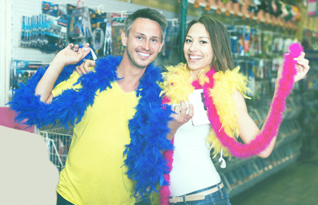 Smiling man with girlfriend wearing feather boa in festive accessories shop