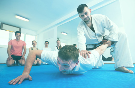 Young european man training new taekwondo holds with adults during class