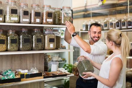 happy young couple choosing dried herbs and spices in organic food store