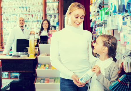 Cheerful mother with a kid in pharmacy and two pharmacists in white coats at the counter at the background
