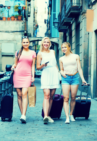 group of joyful smiling traveling girls taking promenade with suitcases in summer city