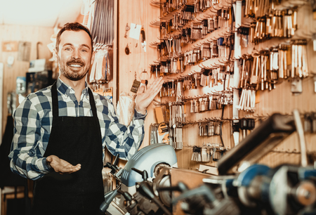 Smiling male worker demonstrating result of his key forming in workpshop