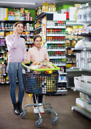 Young smiling   female shopper talking on phone being with teenager in supermarket
