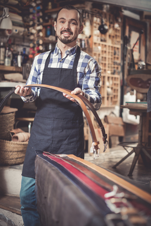 Smiling positive male worker showing new belts in leather workshop
