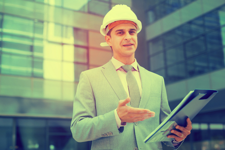 Businessman holding folder with documents and contentedly reading