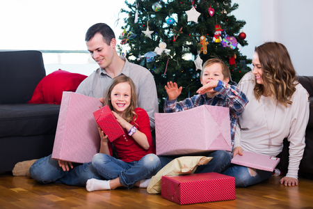 Large happy family handing gifts to each other during Christmas at home